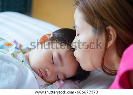 Asian cute little boy patient is sleeping on the sickbed and the face with tears, his mother kissed him on the forehead in the patient room in hospital. Health care medical and people concept.