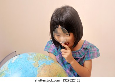 Asian cute little girl feel surprise while looking at globe through magnifying glass.