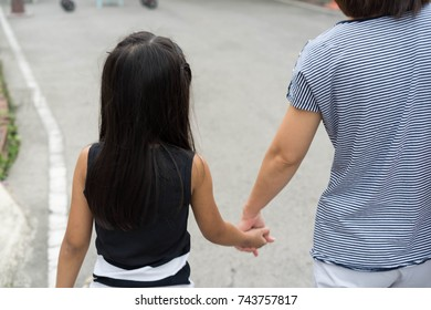 Asian cute little girl Mother hold hands while walking