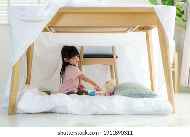 Asian cute little girl play cooking and feeding food to her doll while sitting in a blanket fort in living room at home for perfect hideout away from their other family members.