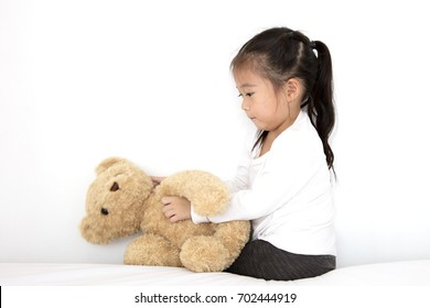 Asian cute little Girl Playing doll teddy bear In the bedroom
