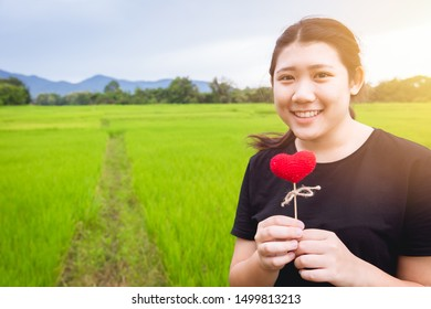 Asian cute teen girl plus size with red heart love green nature background space for text