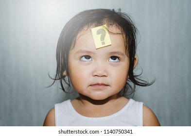 asian cute toddler looking at question mark on her forehead with funny face. child learning and growth concept
