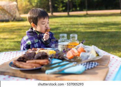An Asian cute young boy eating breakfast outdoor at camping site in nature sunlight with a tent at the background.
