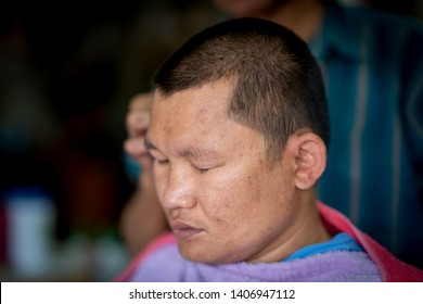 Asian cutting hair in barber shop in countryside or rural, barber holding clipper and comb on head for setting hairstyle of men, short hair skinhead.