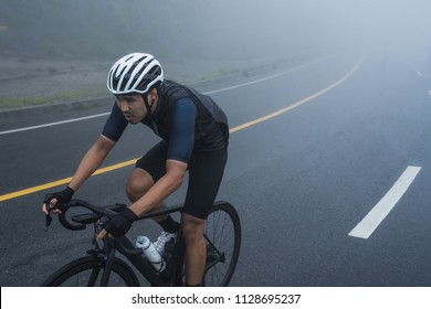 Asian cyclist in blue cycling jersey and white helmet is riding on his bicycle. Morning cycling in a bad weather day; foggy, rainy, windy and cold weather.