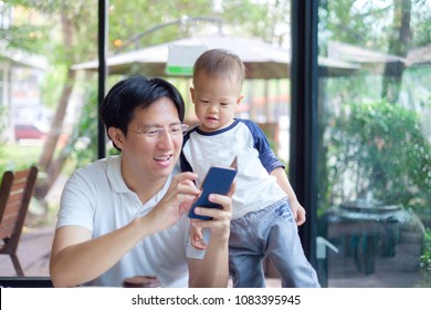 Asian dad and son sitting in city cafe look in the smartphone, Father & Cute little 1 year / 18 months toddler baby boy child spending time together, leisure & technology & internet addiction concept