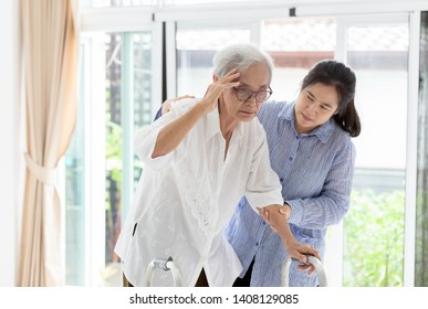 Asian daughter or care assistant helping support senior woman or mother,communicates the symptoms of vertigo;dizziness;migraine;sick depressed,suffering from headache, elderly woman in using walker