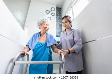 Asian daughter or care assistant service,help,support senior woman taking a shower in bathroom,happy mother walking with walker in bathroom at home,safety of elderly people,family relationship concept
