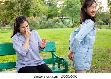 Asian daughter child girl holding her bottom with broke wind,farting all day, bad smell and stinks caused by bloating,flatulence and gas in digestive tract while mother covering his nose,stinky fart