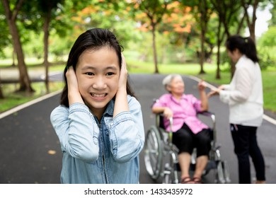 Asian daughter closed ears with hands,child girl did not want to hear parents,grandmother in wheelchair and mother arguing,quarreling in outdoor park,problem in multi generation family,quarrel concept