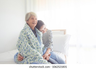 Asian daughter hugging her senior mother in bedroom at home