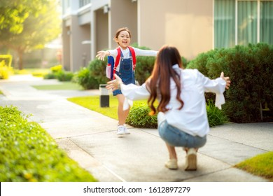 Asian daughter run to her mother after come back from her preschool, this image can use for single mom, school, family, education, home, house and outdoor concept