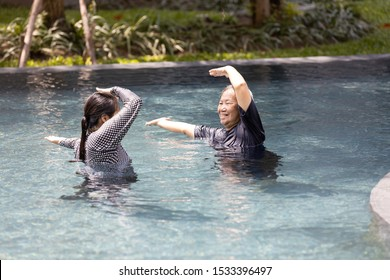 Asian daughter is supporting,care the elderly mother doing water aerobics in sunny day,exercising in the morning,happy and healthy senior woman in swimming pool in summer vacation,health care concept