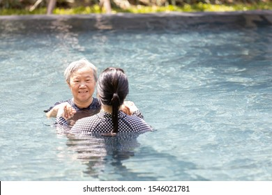 Asian daughter is supporting,care the elderly mother walking in pool on sunny day and exercising in the morning ,happy and healthy senior woman in swimming pool in summer vacation,health care concept