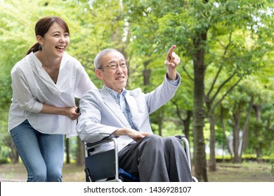 asian daughter walking with disabled father in wheelchair at park