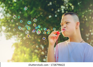 Asian Dawn syndrome boys enjoying outdoors blowing a soap bubbles