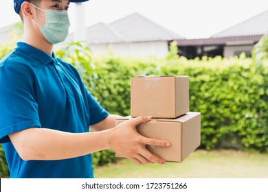 Asian delivery express courier young man use giving boxes to woman customer he wearing protective face mask at front home, under curfew quarantine pandemic coronavirus COVID-19
