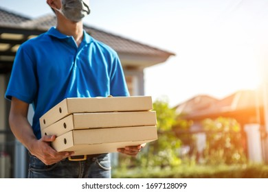 Asian delivery of goods during the prevention of coronovirus, Covid-19. Courier in a face mask with a box in his hands. Portrait from the waist up. Delivery man concept.