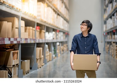 Asian delivery man carrying cardboard box between row of product shelves in warehouse. Inventory picking and packing concept. Shopping lifestyle in department store. Buying or purchasing factory goods