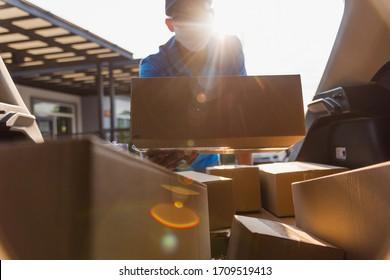 Asiatischer Liefermann-Kurier, der die Auslieferung von Boxen in Rückwagen die Schutzmaske, Service-Kunde im Vorderhaus unter curwenige Quarantäne-Pandemie-Koronavirus COVID-19, in der Auto-Kofferraum-Ansicht