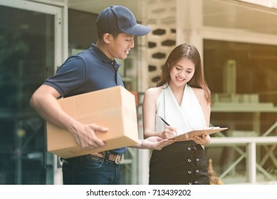Asian delivery man holding a cardboard box while waiting beautiful asian woman putting signature in clipboard for confirm receive.
