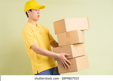 Asian delivery man is holding the carton with him and running to deliver the goods
