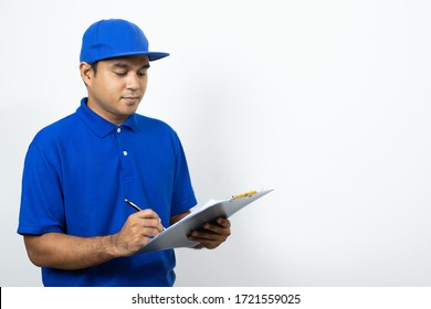 Asian Delivery man signing clipboard receipt of delivery package on isolated white background.
