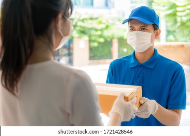 Asian delivery man wearing face mask and glove in blue uniform holding a cardboard boxes in front house and woman accepting a delivery of boxes from deliveryman during COVID-19 outbreak.