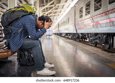 Asian depressed traveler mistakes a train at train station