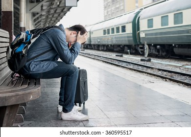 Asian depressed traveler waiting at train station after mistakes a train.
