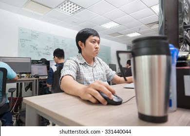 Asian Developer Using Laptop Computer Sitting Desk Working Real Office