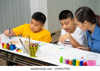 Asian disability boy learning color Painting in classroom with Autism girl in special school with female teacher.