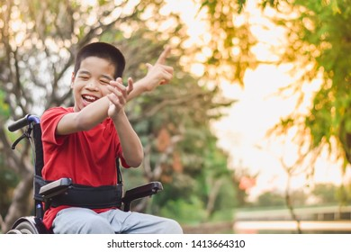 Asian disabled child on wheelchair is play and learn in the outdoor park like other people, Life in the education age of special children, Happy disabled kid concept.