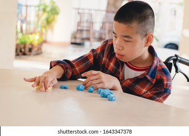 Asian disabled child on wheelchair molding clay, Fun and entertaining activity for training small and large muscles, Lifestyle in the education age of special need kids, Happy disability kid concept.