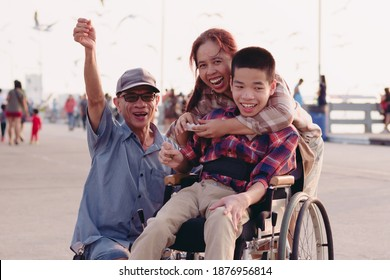 Asian Disabled child on wheelchair and parents the outdoors nature and seagull birds background,Life in the education age of special children,Happy disability kid travel in family holiday concept.