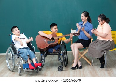 asian disabled children and woman teacher enjoying and playing guitar