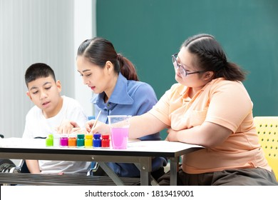 asian disabled kids or autism child learning and painting at paper with teacher helping in classroom