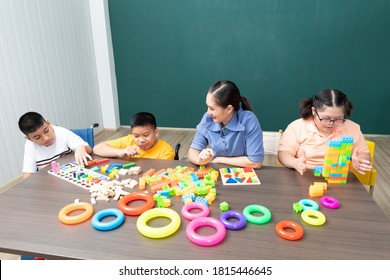asian disabled kids or autism child playing toys with teacher helping in classroom