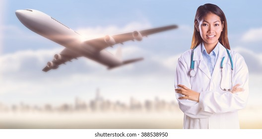 Asian doctor with arms crossed looking at the camera against city on the horizon
