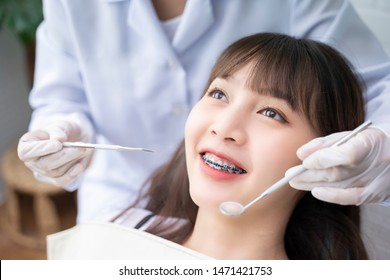 Asian Doctor Dentist examine female patient with braces in a dental office, wearing gloves standing in clinic check Close Up young braces Asian woman, Beautiful Asian girl smiles in dentistry.
