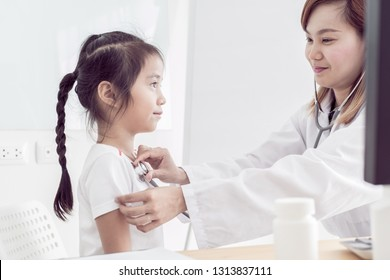 Asian doctor examining a little girl by stethoscope