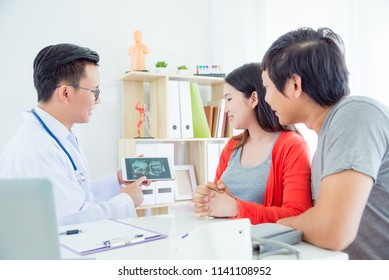 Asian Doctor explain ultrasound result to asian couple at hospital