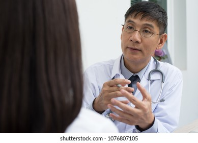 Asian doctor, gynecologist, psychiatrist explaining for female patient at out patient department or consulting room in hospital, close up