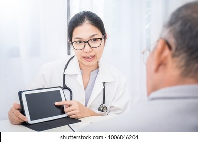 Asian doctor having conversation with her senior patient and holding ipad gadget in medical office. Doctor intern ( woman ) explaining x-ray results to patient