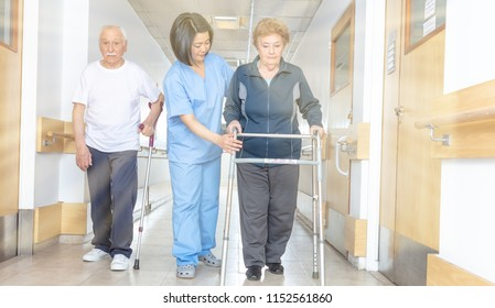 Asian doctor helping elder woman with walker and man in hospital aisle, light rays coming from sky.