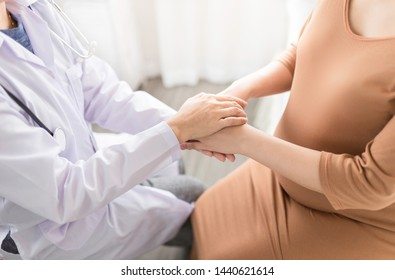 asian doctor holding hand of pregnancy people, they talk about pregnant information, antenatal care activity, hand in hand