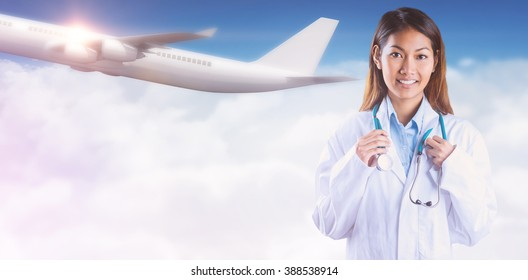 Asian doctor holding stethoscope against bright blue sky over clouds