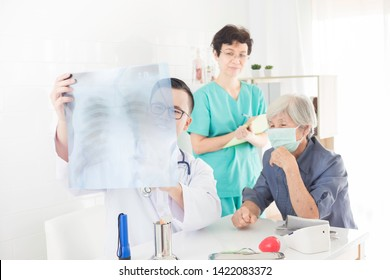 Asian doctor looking patient film, he holding film and talk with patient about disease, broken bone treatment, tuberculosis screening