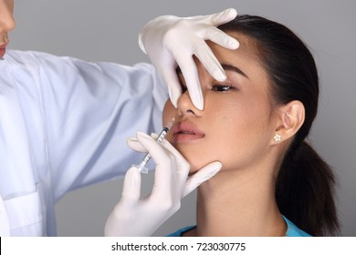 Asian Doctor Nurse check face nose structure before plastic surgery and inject beauty chemical syringe to patient, Studio lighting grey background aesthetics